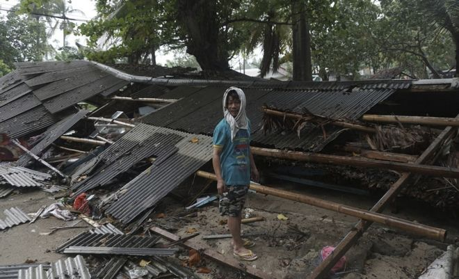 Άνδρας στέκεται μπροστά στο κατεστραμμένο σπίτι του μετά το φονικό τσουνάμι