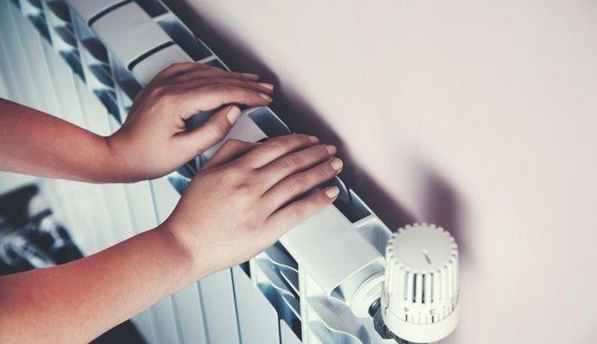 Γυναίκα προσπαθεί να ζεστάνει τα χέρια της στο σπίτι
