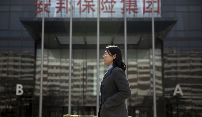 A woman walks past the offices of the Anbang Insurance Group in Beijing, Friday, Feb. 23, 2018. The founder of one of China's biggest insurers, who had discussed possibly investing in a Manhattan skyscraper owned by the family of U.S. President Donald Trump's son-in-law and adviser, will be prosecuted for financial offenses and regulators have taken control of his company, the government announced Friday. (AP Photo/Mark Schiefelbein)