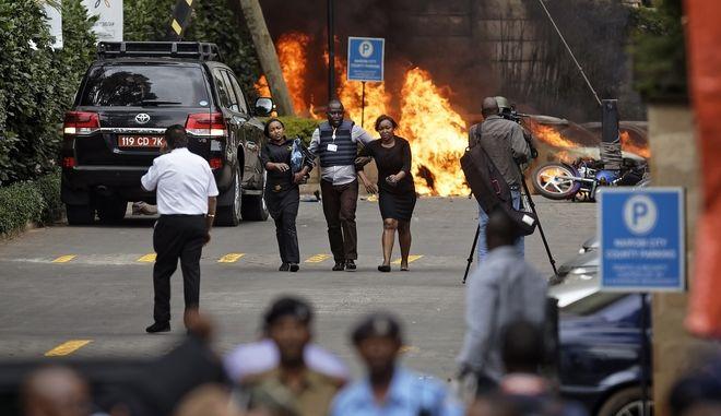 Αστυνομικές δυνάμεις βοηθούν πολίτες να εγκαταλείψουν το σημείο της επίθεσης σε ξενοδοχειακό συγκρότημα στο Ναϊρόμπι