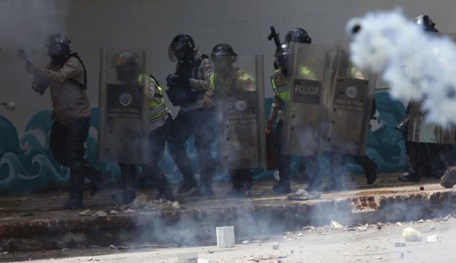 National Police launch tear gas as they advance on student protesters outside the Central University of Venezuela, in Caracas, Thursday, May 4, 2017. Students held demonstrations across Caracas Thursday as a two-month-old protest movement that shows no signs of letting up claimed more lives. (AP Photo/Fernando Llano)