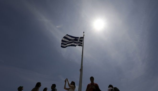 A Greek flag waves as tourists enjoy the view atop of the ancient Acropolis hill in Athens, on Monday, May 9, 2016. European finance ministers are trying to break a deadlock over whether to provide Greece with the next batch of bailout loans, which it needs to avoid bankruptcy this year, and forgive some of its debts. (AP Photo/Thanassis Stavrakis)