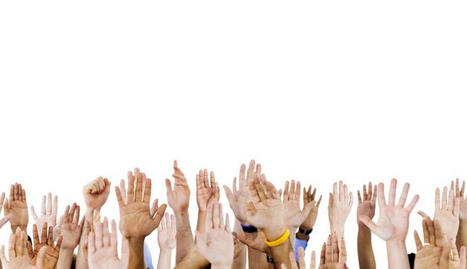 Multi ethnic people's hands raised.