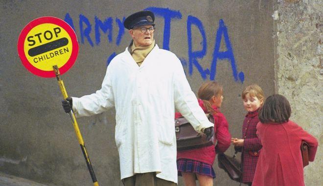 "Armored patrols by British troops and schools crossing ""lollipop"" man in Londonderry, Northern Ireland in Feb. 1972.  IRA graffiti on walls, etc. (AP Photo/Michel Laurent)"