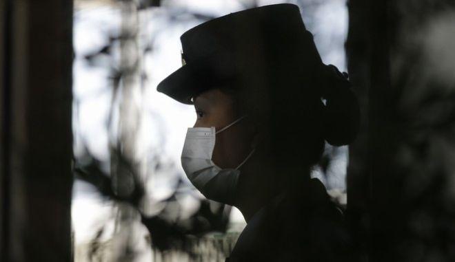 Γυναίκα αστυνομικός φορά μάσκα στο αεροδρόμιο της Μανίλα