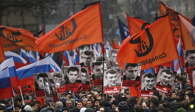 People march in memory of opposition leader Boris Nemtsov, who was gunned down on Friday, Feb. 27, 2015, near the Kremlin with portraits of him and words reading ' those bullets for everyone of us, heroes never die!  in Moscow, Russia, Sunday, March 1, 2015. Russian investigators, politicians and political commentators on state television on Saturday covered much ground in looking for the reason Nemtsov was gunned down in the heart of Moscow, but they sidestepped one possibility, that he was murdered for his relentless opposition to Putin. (AP Photo/Dmitry Lovetsky)
