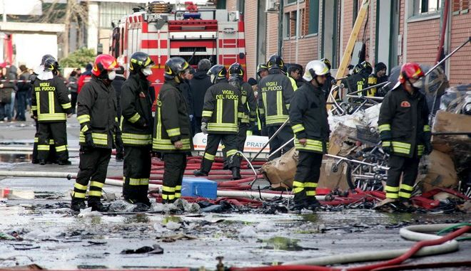 Firefighters inspect the area where a fire broke out in a Chinese-run garment factory in Prato, near Florence, Italy, Sunday, Dec. 1, 2013. A fire early Sunday swept through an illegal, makeshift dormitory in a Chinese-run garment factory in Tuscany, killing seven, firefighters said. The blaze, which partially collapsed the factory's roof, broke out in a loft where 11 people were sleeping, said fire inspector Stefano Giannelli. The cause was under investigation. Two people remained hospitalized, while two were treated and released, Giannelli said. The Tuscan city of Prato has become a center for Chinese-run factories producing low-cost garments mostly for international retailers, an activity that has all but decimated Italy's own lower-end clothing industry. Many of the workers aren't declared to authorities, sleeping, eating and living in the factories where they work. (AP Photo/Stringer)