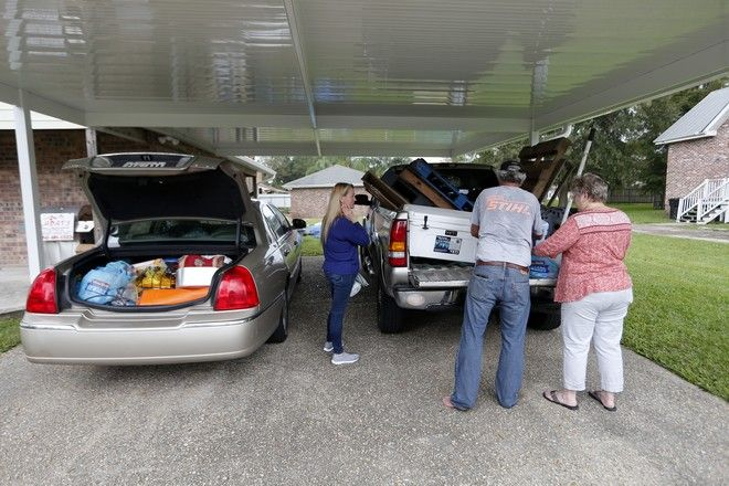 Larry Bartron and Kimberlee Bartron, right, load goods in their vehicles with the help of their friend, Vickie Strickland, vacationing from Indiana, as they evacuate Braithwaite, La., in preparation for Hurricane Nate, expected to make landfall on the Gulf Coast, Saturday, Oct. 7, 2017. (AP Photo/Gerald Herbert)