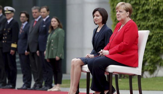 Η Άγγελα Μέρκελ και η πρωθυπουργός της Μολδαβίας Μάια Σάντου παρέμειναν καθιστές κατά την ανάκρουση των εθνικών ύμνων των χωρών τους στην ομοσπονδιακή καγκελαρία στο Βερολίνο