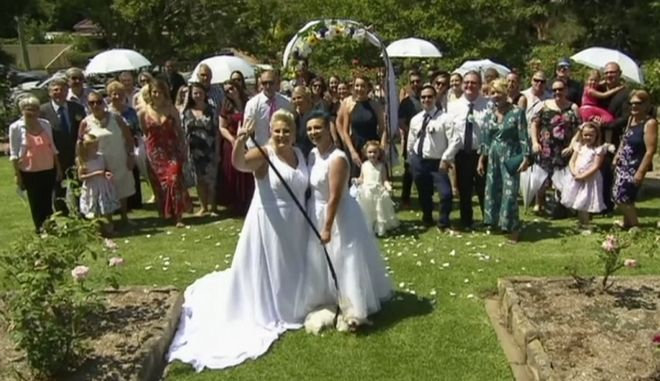 In this image made from video, newlywed couple, Amy Laker, center left, and Lauren Price, center right, pose for a photo during their ceremony in Sydney, Saturday, Dec. 16, 2017.  Two female couples tied the knot in Australia's first same-sex weddings under new legislation allowing gay marriages.  January 9 had been expected to be the first possible date for same-sex weddings due to a four-week waiting period since the landmark law was passed. But the two couples were married in Sydney and Melbourne on Saturday after being granted permission to waive the notice period. Amy Laker, 29, and Lauren Price, 31, exchanged vows in Sydney because their families had to travel from Wales in the U.K. to attend what was to have been their commitment ceremony. (Channel 9 via AP)