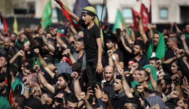 Lebanese Shiite supporters of Hezbollah shouts slogans against the U.S and Israel during activities marking the holy day of Ashoura, in southern Beirut, Lebanon, Sunday, Oct. 1, 2017. Ashoura is the annual Shiite Muslim commemoration marking the death of Imam Hussein, the grandson of the Prophet Muhammad, at the Battle of Karbala in present-day Iraq in the 7th century. (AP Photo/Hassan Ammar)