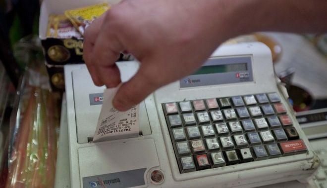 Πελάτης παραλαμβάνει την απόδειξη σε κατάστημα