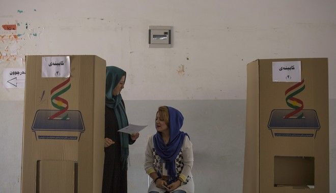 A volunteer looks at a voter's ballot as she walks out of a voting booth in the disputed city of Kirkuk, Monday Sept. 25, 2017. Millions are expected to vote on Monday in Iraq's Kurdish-run provinces and disputed territories as Iraqi Kurds cast ballots in support for independence from Baghdad in a historic but non-binding vote. (AP Photo/Bram Janssen)