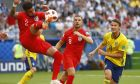 England's Kyle Walker, left, kicks the ball front of England's Jordan Henderson, center, and Sweden's Albin Ekdal, right, during the quarterfinal match between Sweden and England at the 2018 soccer World Cup in the Samara Arena, in Samara, Russia, Saturday, July 7, 2018. (AP Photo/Matthias Schrader )