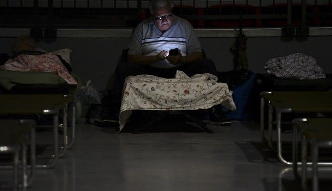A man watches his cell phone while waiting at Humacao Arena refugee center for the imminent impact of Maria, a Category 5 hurricane that threatens to hit the eastern region of the island with sustained winds of 175 miles per hour, in Humacao, Puerto Rico, Tuesday, September 19, 2017. About 137 citizens arrived at the refuge from different parts of the eastern region of the Island. (AP Photo/Carlos Giusti)
