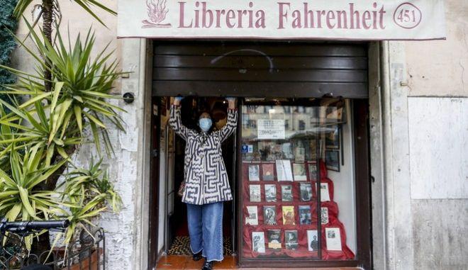 Γυναίκα στην Ρώμη ξανά ανοίγει το βιβλιοπωλείο της ύστερα από τη σταδιακή άρση των μέτρων