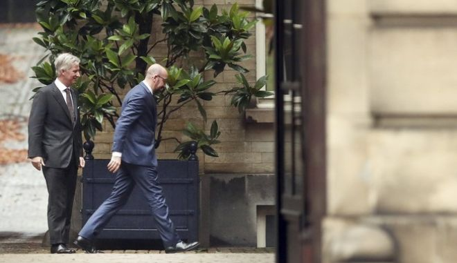 Belgium's Prime Minister Charles Michel, right, walks away after meeting with Belgium's King Philippe, left, during consultations at the Royal Palace in Brussels, Friday, Dec. 21, 2018. Prime Minister Charles Michel holds talks with Belgium's King Philippe as the monarch weighs whether to accept the premier's resignation and name him at the head of a caretaker government until elections are held in May. (AP Photo/Francisco Seco)