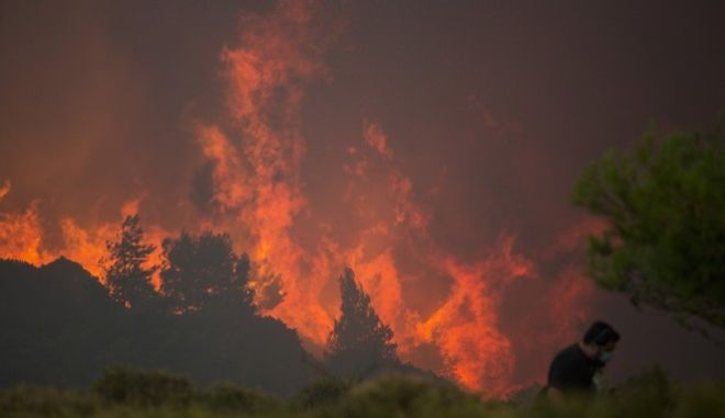 A man walks in front of huge blaze during a forest fire near the village of Varnava , north of Athens, on Monday, Aug. 14, 2017.A large wildfire north of Athens is threatening homes as it sweeps through pine forest for a second day, uncontained due to high winds. (AP Photo/Petros Giannakouris)