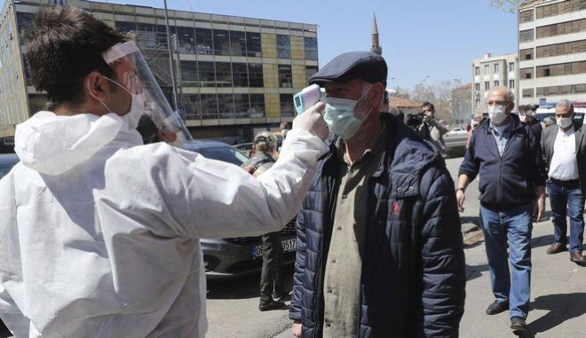 Υγειονομικός ελέγχει την θερμοκρασία ενός άνδρα στην Άγκυρα (AP Photo)