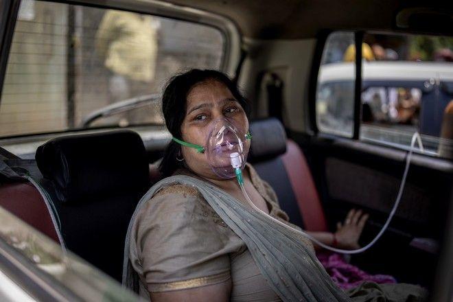 Γυναίκα με κορονοϊό φοράει μάσκα οξυγόνου σε όχημα της Ινδίας