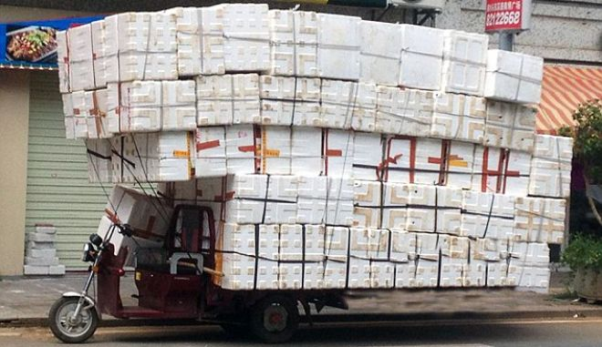 """Pic shows: The overloaded tricycle with the boxes.  A woman nearly caused a pile up by loading her tricycle with scores of empty cardboard boxes.  Stunned motorists had to give her a wide birth as she fastened on the boxes  in the city of Dongguan, south Chinas Guangdong Province.  Witnesses said some 200 empty plastic boxes were tied to the tricycle, which would have been considered a serious traffic violation, had she been caught by police.  The small tricycle looked like  a lorry  after the woman  had finished her handiwork.  Some passing motorists actually stopped  to take photos  while others took a wide berth in case the boxes came tumbling down onto their cars. Pictures of her laden down transport quickly went viral on Chinese social media.  One called her  the """"snail woman"""" because she waould have to drive so slowly.  Another asked : """"What if the boxes collapse on her while shes riding the tricycle?""""  Someone else said:: """"At least the boxes are empty.""""  Another commented:""""I hope it doesnt rain.""""  (ends)"""