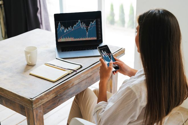 Attractive business woman sits at table in front of laptop and uses smartphone for work. Beautiful brunette girl analyzes stock market while at home. Millennial women on Internet.