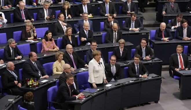 German Chancellor Angela Merkel, center, confirms the vote after she was elected for a fourth term as chancellor at Germany's parliament Bundestag in Berlin, Germany, Wednesday, March 14, 2018. (AP Photo/Markus Schreiber)