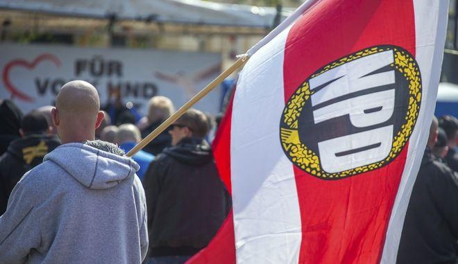 ARCHIVO - En esta imagen de archivo del 1 de mayo de 2016, un hombre con una bandera del Partido Nacional Democrático, o NPD, en un mitin en Schwerin, Alemania. (Jens Buettner/dpa via AP,file)