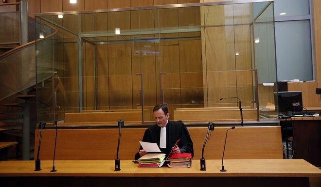 Carlos the Jackal's lawyer Francis Vuillemin, reads files at the Paris court, France, Monday, March 13, 2017. The Venezuelan-born Ilich Ramirez Sanchez known as Carlos the Jackal is appearing in a French court for a deadly 1974 attack against a Paris shopping arcade, a trial that victims' families have been awaiting for decades. (AP Photo/Christophe Ena)