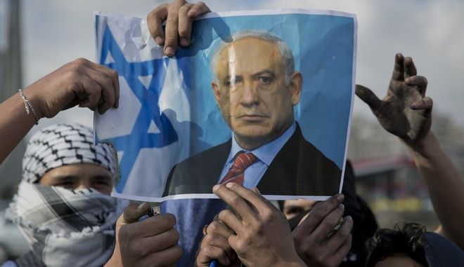 Palestinian protesters are about to burn a poster with a picture of Israeli Prime Minister Benjamin Netanyahu during clashes with Israeli troops following protests against U.S. President Donald Trump's decision to recognize Jerusalem as the capital of Israel, in the West Bank city of Ramallah, Thursday, Dec. 14, 2017. (AP Photo/Nasser Nasser)