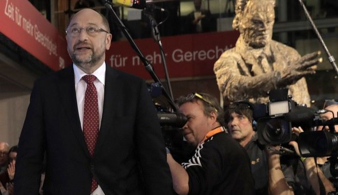 SDP party chairman and top candidate Martin Schulz walk onto the stage as a statue of chancellor Willy Brandt is seen in the background at the headquarters of the Social Democratic party in Berlin, Germany, Sunday, Sept. 24, 2017, after the polling stations for the German parliament elections had been closed. (AP Photo/Gero Breloer)