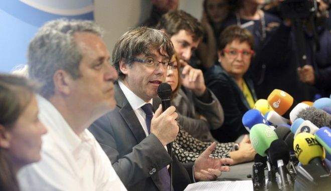 Sacked Catalonian President Carles Puigdemont, center, speaks during a press conference in Brussels, Tuesday, Oct. 31, 2017. Ousted Catalan President Carles Puigdemont is calling for avoiding violence and says dialogue is a priority during his first address on Belgian soil. Puigdemont on Tuesday recapped the issues which led him to leave for Belgium the previous day, but did not immediately say in his statement what he would do in Brussels or whether he would seek asylum. (AP Photo/Olivier Matthys)