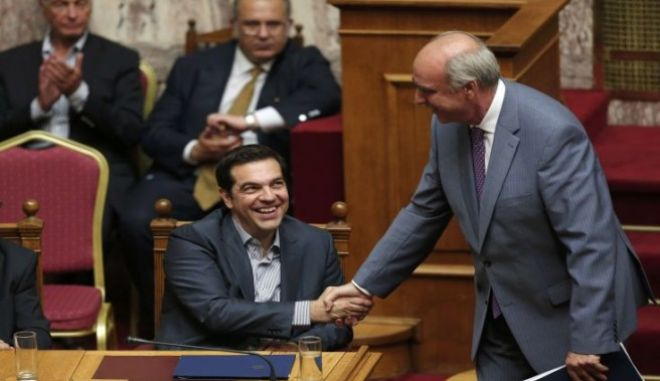 Greek Prime Minister Alexis Tsipras shakes hands with leader of main opposition New Democracy conservative party Evangelos Meimarakis after delivering his speech during a parliamentary session in Athens, Greece, July 10, 2015. Greek Prime Minister Alexis Tsipras appealed to his party's lawmakers on Friday to back a tough reforms package after abruptly offering last-minute concessions to try to save the country from financial meltdown.            REUTERS/Alkis Konstantinidis