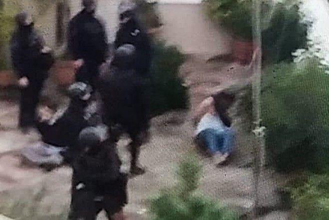 Η στιγμή που αστυνομικοί ακινητοποιούν τους ιδιοκτήτες του οικήματος, δίπλα από το υπό κατάληψη κτήριο