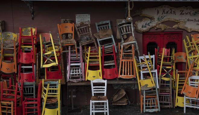 Αναποδογυρισμένες καρέκλες έξω από κλειστό μαγαζί στο κέντρο της Αθήνας