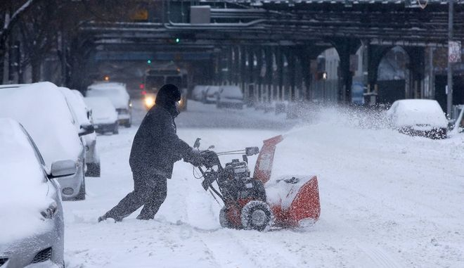 A man clears snow with a snow blower in the South Bronx section of New York City, January 3, 2014. A major snowstorm producing blizzard-like conditions hammered the northeastern United States on Friday, causing more than 1,000 U.S. flight delays and cancellations, paralyzing road travel, and closing schools and government offices.  REUTERS/Mike Segar  (UNITED STATES - Tags: ENVIRONMENT SOCIETY) ORG XMIT: NYK302