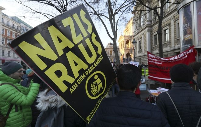 A demonstrator holds a poster 'Nazis out of the parliament' during a demonstration prior to the swearing-in ceremony of the new Austrian government led by a conservative and a nationalist party in Vienna, Austria, Monday, Dec. 18, 2017. (AP Photo/Ronald Zak)
