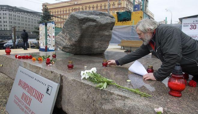 Άνδρας ανάβει ένα κερί στο μνημείο για τα θύματα του σταλινικού καθεστώτος στην πλατεία Λιουμπιάνκα στη Μόσχα.