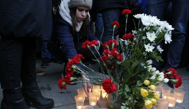 People light candles at an entrance of the Sennaya subway station after an explosion in the subway in St.Petersburg, Russia, Monday, April 3, 2017. A bomb blast tore through a subway train in Russia's second-largest city Monday, killing several people and injuring many more as President Vladimir Putin was visiting St. Petersburg, authorities said. (AP Photo/Elena Ignatyeva)