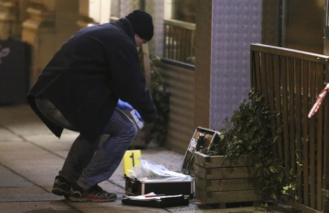 A forensic expert secures evidence after several people have been injured in a knife attack on the streets of Vienna, Austria, Wednesday, March 7, 2018. (AP Photo/Ronald Zak)