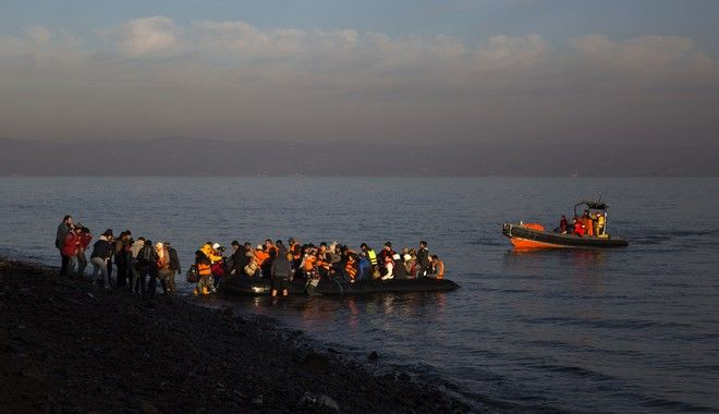 Refugees and migrants disembark from a dinghy on a beach after crossing a part of the Aegean sea from the Turkey's coast to the northeastern Greek island of Lesbos, on Friday, Dec. 25, 2015. The International Organization for Migrants said more than 1 million people have entered Europe earlier this week. Almost all came by sea, while 3,692 drowned in the attempt. (AP Photo/Santi Palacios)