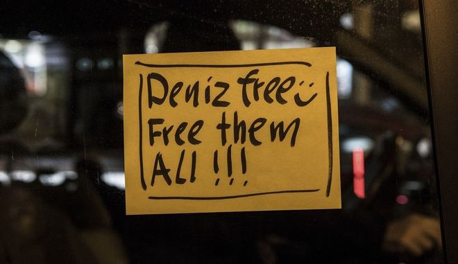"A sticker ""Deniz free - free them all"" is attached to a window during a car parade in Berlin, Friday, Feb. 16, 2018 on the day when Deniz Yucel, a correspondent for the German daily Die Welt, who was detained as part of a Turkish government clampdown on civil society, was released after more than one year in prison. (Paul Zinken/dpa via AP)"