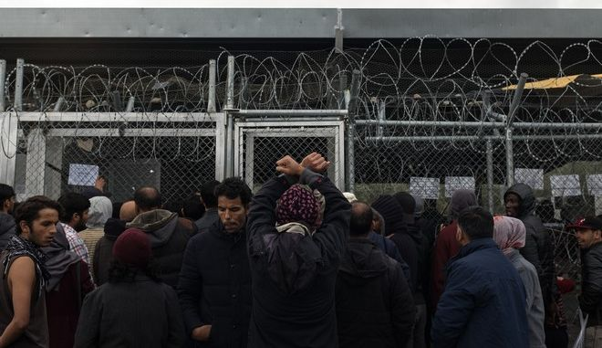A man gestures as people queue outside the registration center of the Greek Asylum service, inside the Moria camp on the island of Lesbos, Greece, on November 28, 2017 /        ,  ,  28 , 2017
