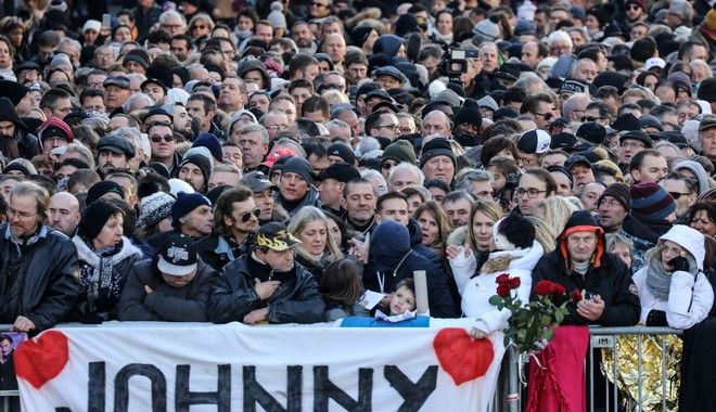 The crowd gather outside the Madeleine church prior to the funeral ceremony to late French rock singer Johnny Hallyday, Saturday Dec. 9, 2017 in Paris. France is bidding farewell to its biggest rock star, honoring Johnny Hallyday with an exceptional funeral procession down the Champs-Elysees, a presidential speech and a parade of motorcyclists  all under intense security. (Ludovic Marin, Pool via AP)