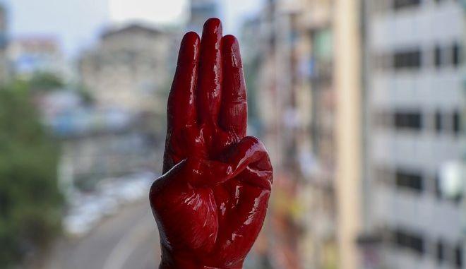 Διαδηλωτής κατά του πραξικοπήματος στη Μιανμάρ κάνει τον χαιρετισμό της αντίστασης έχοντας βάψει  το χέρι του κόκκινο
