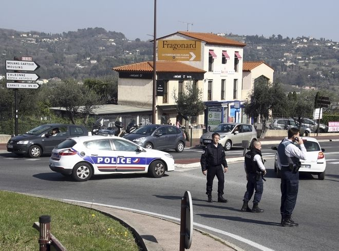 Police officers take position after an attack in a high school student in Grasse, southern France, Thursday, March 16, 2017. An armed high school student was arrested and police fanned out around a picturesque perfume capital in southern France after a school shooting that left at least two wounded. (AP Photo/Philippe Farjon)