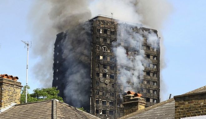 Smoke billows from from a high-rise apartment building on fire in London, Wednesday, June 14, 2017. A massive fire raced through the 27-story high-rise apartment building in west London early Wednesday, sending at least 30 people to hospitals, emergency officials said. (Rick Findler/PA via AP)