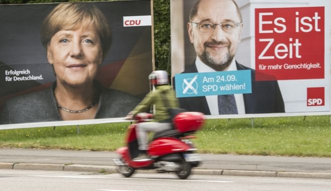 Election posters showing German Chancellor Angela Merkel, CDU, and and social democrat challenger Martin Schulz, SPD, stand at a street in Erfurt, central Germany, Friday, Sept. 15, 2017. Letters read 'Successful for Germany', left, and 'It is time for more fairness'. General election will held in Germany Sept. 24, 2017. (AP Photo/Jens Meyer)