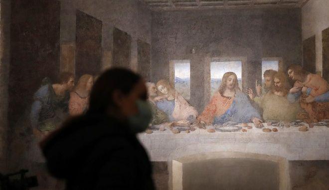 """Γυναίκα με μάσκα μπροστά στον """"Μυστικό Δείπνο"""" του Λεονάρντο ντα Βίντσι, στο Μιλάνο"""