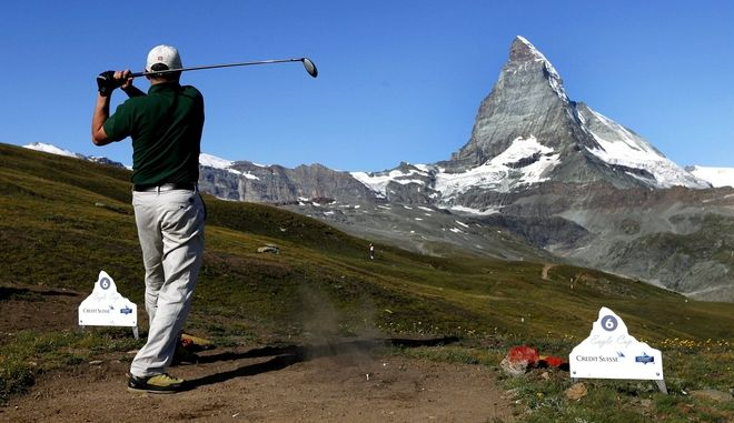 A golfer tees off with the Matterhorn mountain in background at the 18th Matterhorn Eagle Cup on the Riffelberg mountain above Zermatt, Switzerland, Saturday, Aug. 15, 2009. The golfers play this tournament with the original Scottish style, without fairways or perfectly mown greens in an alpine landscape. (AP Photo/Keystone, Jean-Christophe Bott)
